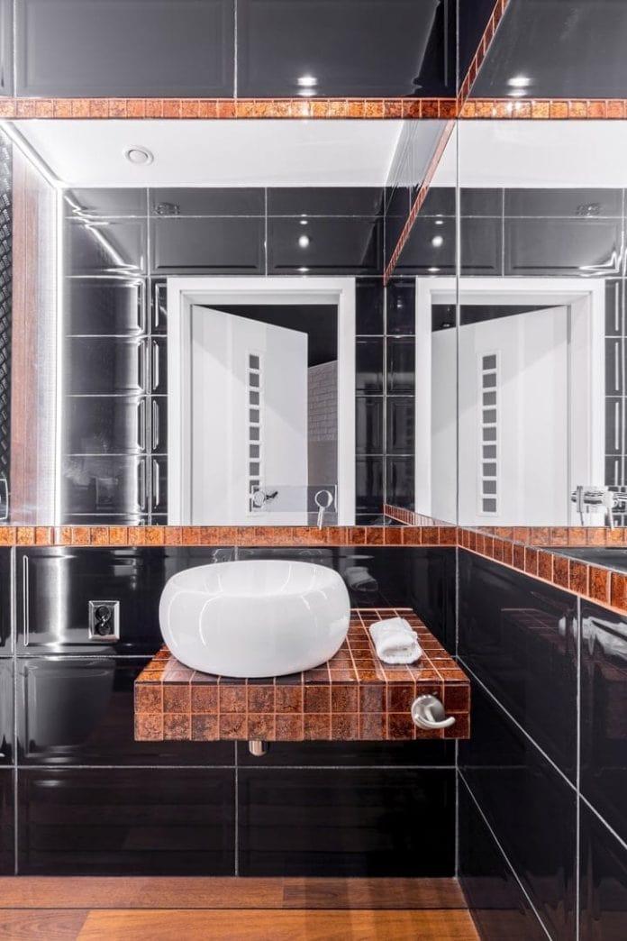 Mała łazienka z dobrym oświetleniem i lustrami powiększającymi optycznie przestrzeń