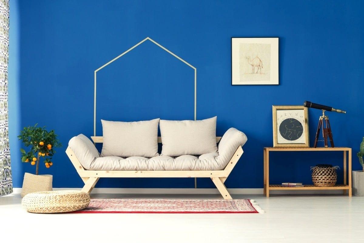 Pełna charakteru niebieska ściana jako idealne tło dla jasnych, prostych mebli