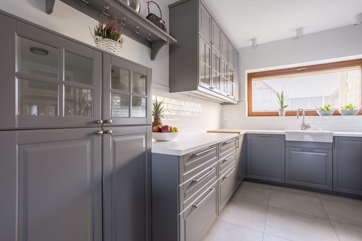 Połączenie szarości szafek, białych ścian i blatów oraz dużych płytek podłogowych daje bardzo dobry efekt
