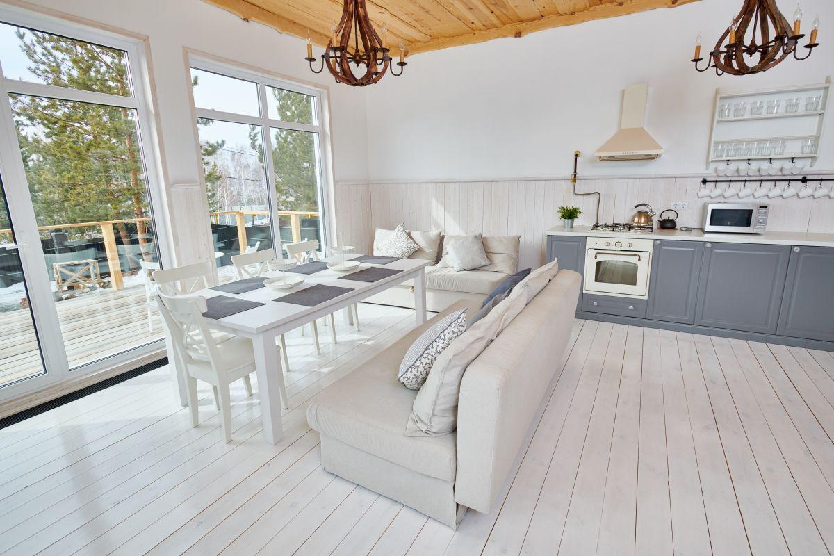 Szare szafki kuchenne połączone z bielonym drewnem podłogi