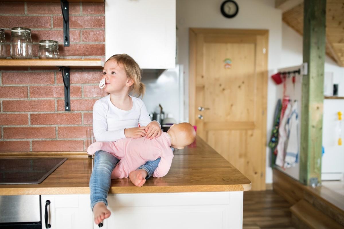 Odsłonięte belki, drewno na podłodze, drewniane drzwi i takież blaty - harmonijna całość w kuchni na poddaszu