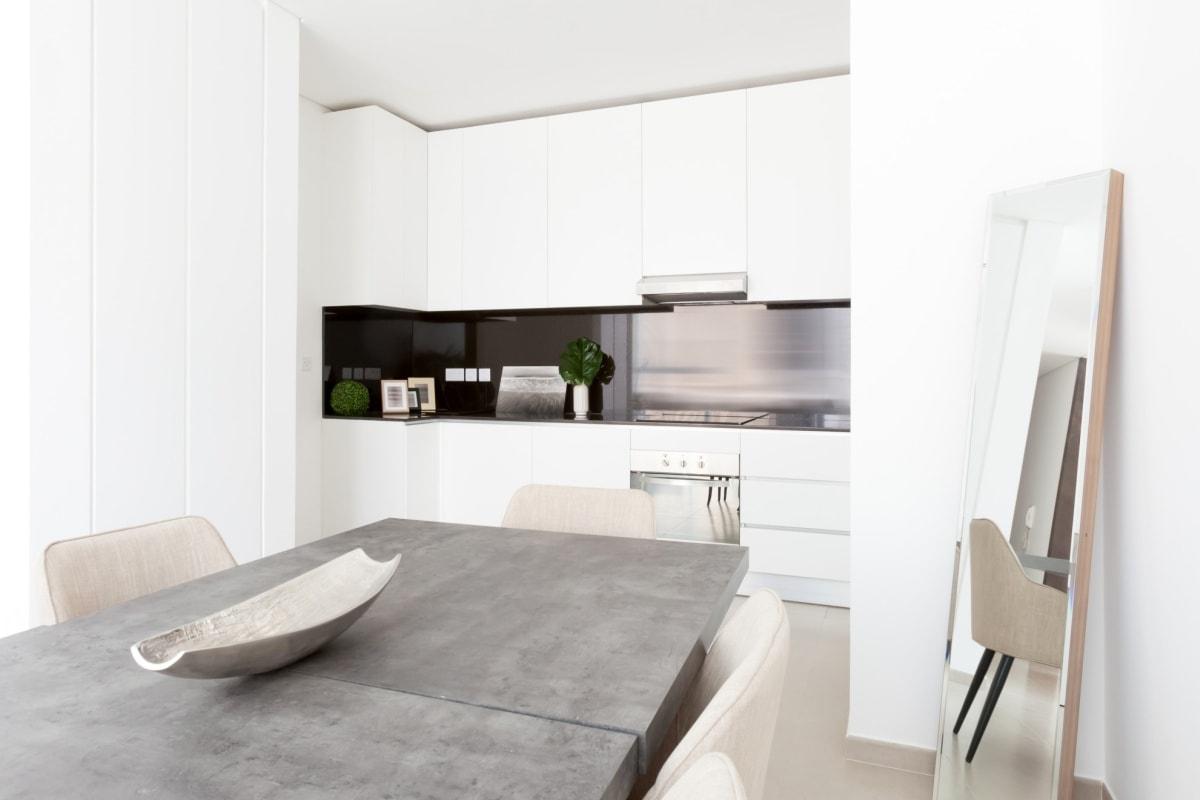 Prosta, ascetyczna wręcz kuchnia znika na tle białych ścian…