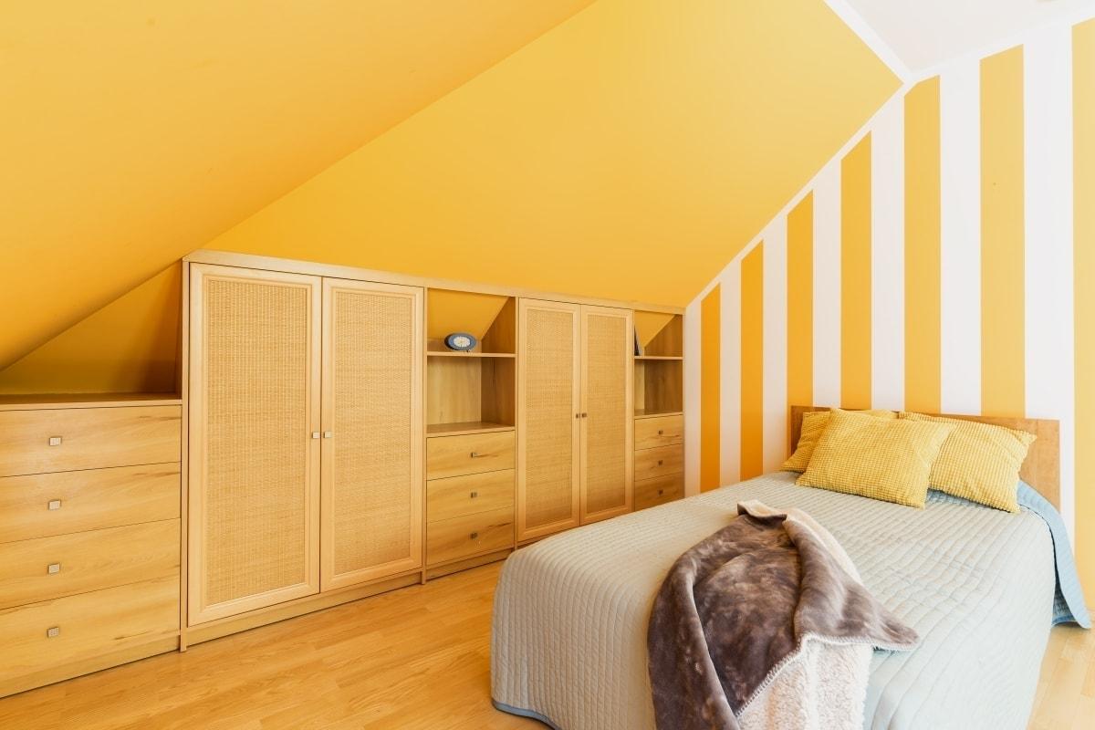 W sypialni na poddaszu miejsce ze skosami wykorzystujemy na szafki i garderobę