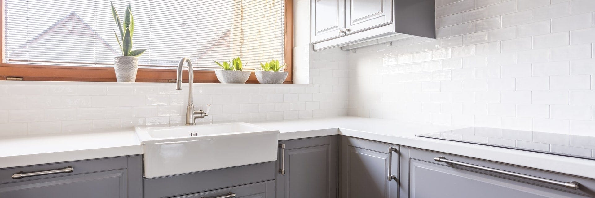 Szara kuchnia i biały blat z konglomeratu - proste i eleganckie połączenie
